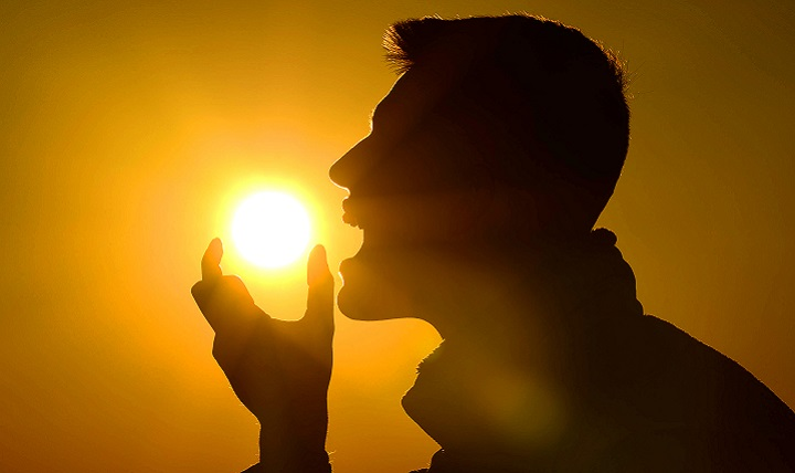 Senior Airman Michael Cossaboom, 20th Fighter Wing Public Affairs photojournalist, pretends to eat the sun during a sunrise in Asheville N.C., April 18, 2016. Finding ways to enjoy the workday keeps morale high for Airmen and their counterparts. (U.S. Air Force photo by Senior Airman Jensen Stidham)
